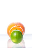 Tangerine, grapefruit and lime on black plate isolated on white Royalty Free Stock Photos
