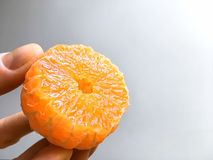 Tangerine in hand against grey background, tangerine peeled and cut in half, close-up,soft focus. Tangerine in hand against grey background, tangerine peeled and stock photography