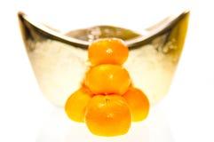 Tangerine with ingot background Royalty Free Stock Photos