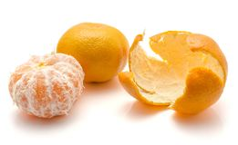 Tangerine isolated on white. Peeled tangerine with separated rind and one whole isolated on white background royalty free stock photography