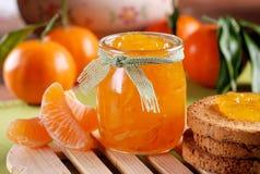 Tangerine jam in glass jar. With fruit around Stock Photography
