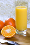 Tangerine juice. Glass of fresh squeezed tangerine juice with tangerines and a knife Royalty Free Stock Photography