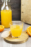 Tangerine juice in glass and fresh fruit on a wooden background Royalty Free Stock Photos
