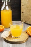 Tangerine juice in glass and fresh fruit on a wooden background. Stock Image