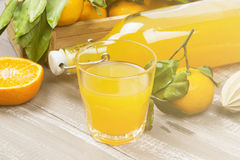 Tangerine juice in glass and fresh fruit on a wooden background. Stock Photos