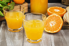 Tangerine juice in glass and fresh fruit on a wooden background. Royalty Free Stock Images