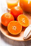Tangerine juice. The preparation for tangerine juice for breakfast. Wooden  citrus reamer with fruits Royalty Free Stock Photos