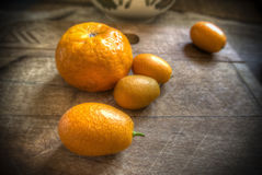 Tangerine and kumquat. A tangerine and some kumquat on a wooden board Stock Photography