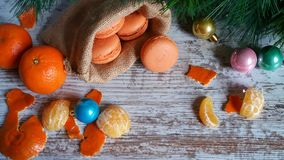 Tangerine macarons at Christmas time. Tangerine macarons in jute sack and Christmas tree decorations on old wooden background Royalty Free Stock Images