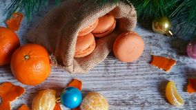 Tangerine macarons at Christmas time. Tangerine macarons in jute sack and Christmas tree decorations on old wooden background Stock Image