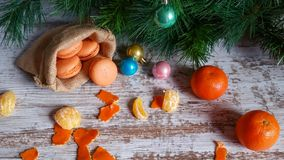 Tangerine macarons at Christmas time. Tangerine macarons in jute sack and Christmas tree decorations on old wooden background Royalty Free Stock Photo