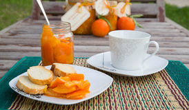 Tangerine marmalade and a cup of warm milk Royalty Free Stock Photo