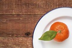 Tangerine on metal enamel plate Royalty Free Stock Image