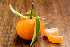 Tangerine mit Blättern und Scheiben Lizenzfreie Stockbilder