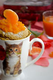 Tangerine muffin cooked in a microwave oven in a white cup with a picture of a kitten Royalty Free Stock Photography