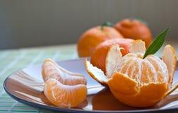 Tangerine na brązu talerzu z łupą i segmentami Obrazy Stock