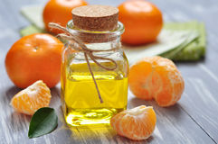 Tangerine oil in a glass bottle. With fresh tangerine  wooden background Stock Photos