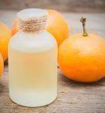 Tangerine olej w szklanej butelce z świeżymi tangerines na drewnianym Fotografia Royalty Free