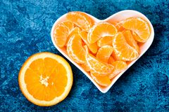 Tangerine and orange in white heart shaped plate stock photography