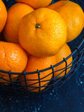Tangerine orange in wire basket Dark Background. Stock Image