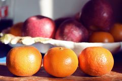 Tangerine oranges lined up in kitchen with fruit basket in the back royalty free stock images
