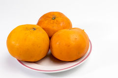 Tangerine on a plate having pink rim royalty free stock photography