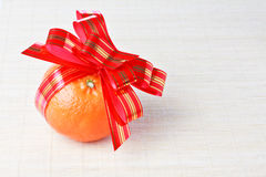 Tangerine with red goldish striped bow as a gift Stock Photography