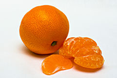 Tangerine. A ripe tangerine with slices on white background Royalty Free Stock Image