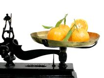 Tangerine on a scale. Tangerine with leaves on a scale tray royalty free stock photo