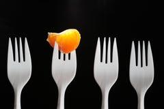 Tangerine Segment. Four white plastic forks on dark. One fork with tangerine segment Royalty Free Stock Image