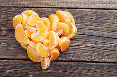 Tangerine in the shape of hearts. Slices of tangerine in the shape of hearts on wooden background Stock Photo