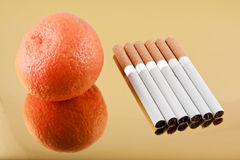 Tangerine or six cigarettes. Good or bad habit Stock Photos