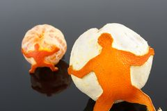 Tangerine skin man. Figure of man of tangerine skin pushing a big tangerine over grey Royalty Free Stock Photos