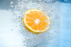 Tangerine slice. In blue Royalty Free Stock Images