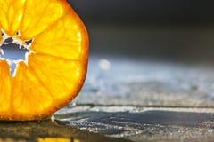 Tangerine slice on wooden background, back lighted Stock Image