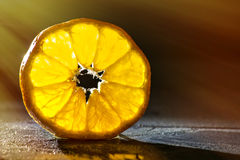 Tangerine slice on wooden background, back lighted Stock Photo