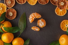 Tangerine slices decompose at the edges of the slate table Stock Images