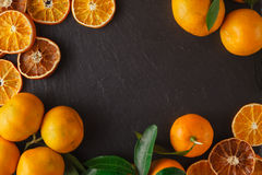 Tangerine slices decompose at the edges of the slate table Stock Photos