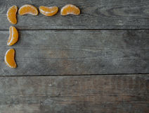 Tangerine slices on wooden background Royalty Free Stock Photography