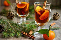 Tangerine tea with cinnamon. Hot tangerine tea with cinnamon on winter background Stock Photo