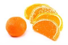 Tangerine- und Fruchtsüßigkeitsegmente auf einer Weißrückseite Stockfoto