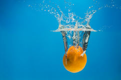 Tangerine in water with splashes on a blue background Royalty Free Stock Images