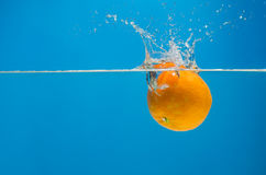 Tangerine in water with splashes on a blue background Royalty Free Stock Photo