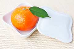 Tangerine on white plate with cover Stock Images