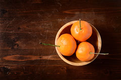 Tangerine in a  wooden bowl on dark wooden table. Top view Royalty Free Stock Photo