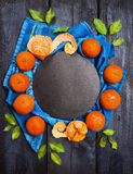 Tangerine wreath whit green leaves on dark wooden with slate and blue towel, food background Stock Image