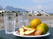 Tangerinen, Äpfel mit einem Glas Wasser auf dem Strand Stockfotografie