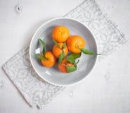 Tangerinen auf weißem hölzernem Hintergrund Graue Serviette Stockfotografie