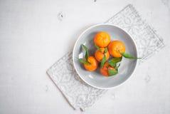 Tangerinen auf weißem hölzernem Hintergrund Graue Serviette Stockbilder