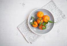 Tangerinen auf weißem hölzernem Hintergrund Graue Serviette Stockfoto